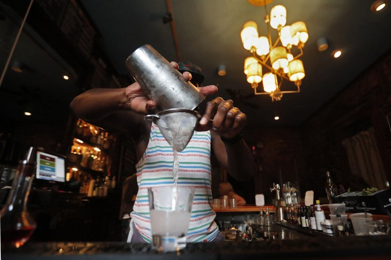 A bartender makes a cocktail in New Orleans. Reports finds if you decide to have an alcoholic drink, limiting yourself to one a day is best — whether you're a man or woman. (AP Photo/Gerald Herbert)