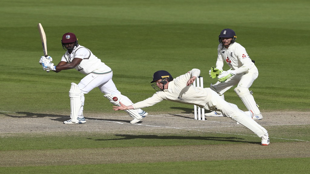 England's Ollie Pope, center, dives to take the catch to dismiss West Indies' Kemar Roach, left, during the last day of the second cricket Test match between England and West Indies at Old Trafford in Manchester, England, Monday, July 20, 2020. (Michael Steele/Pool via AP)