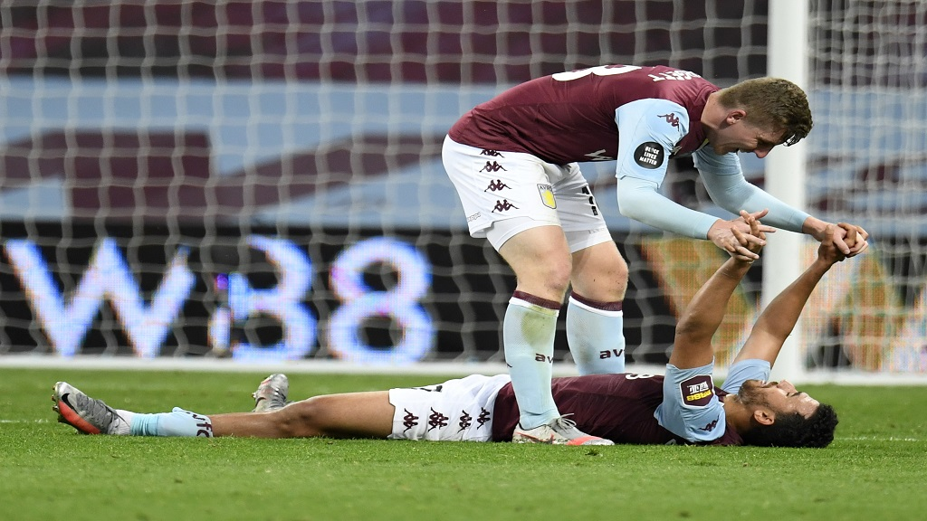 Aston Villa's Matt Targett, top, celebrates with teammate Trezeguet after the English Premier League football match against Arsenal at Villa Park in Birmingham, England, Tuesday, July 21, 2020. (AP Photo/Peter Powell,Pool).