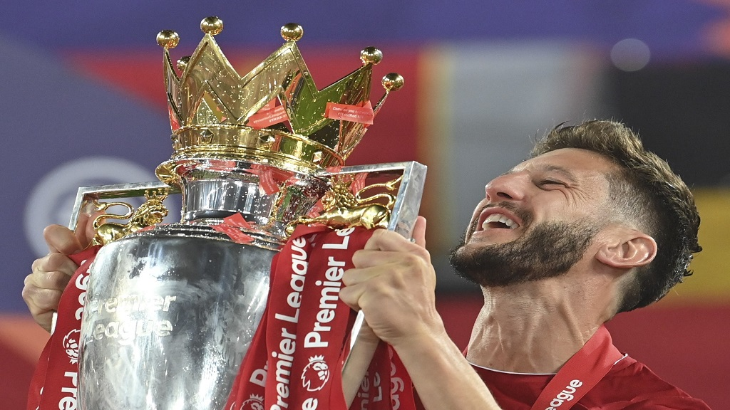 Liverpool's Adam Lallana celebrates with the English Premier League trophy. The trophy was presented to Liverpool following their English Premier League match against Chelsea at Anfield Stadium in Liverpool, England, Wednesday, July 22, 2020.  (Paul Ellis, Pool via AP).