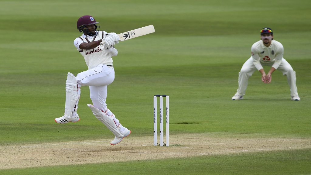 West Indies' Kraigg Brathwaite, left, hits a boundary during the third day of the first cricket Test match against England at the Ageas Bowl in Southampton, England, Friday, July 10, 2020. (Mike Hewitt/Pool via AP) (Mike Hewitt/Pool via AP).