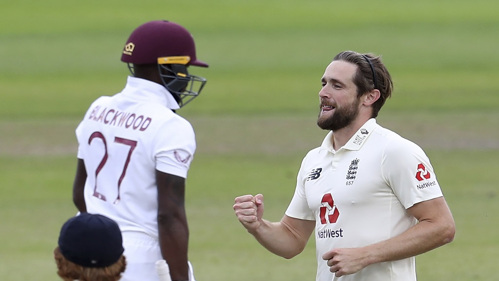 England's Chris Woakes, right, celebrates the dismissal of West Indies' Jermaine Blackwood, left, during the second day of the third cricket Test match  at Old Trafford in Manchester, England, Saturday, July 25, 2020. (Martin Rickett/Pool via AP).