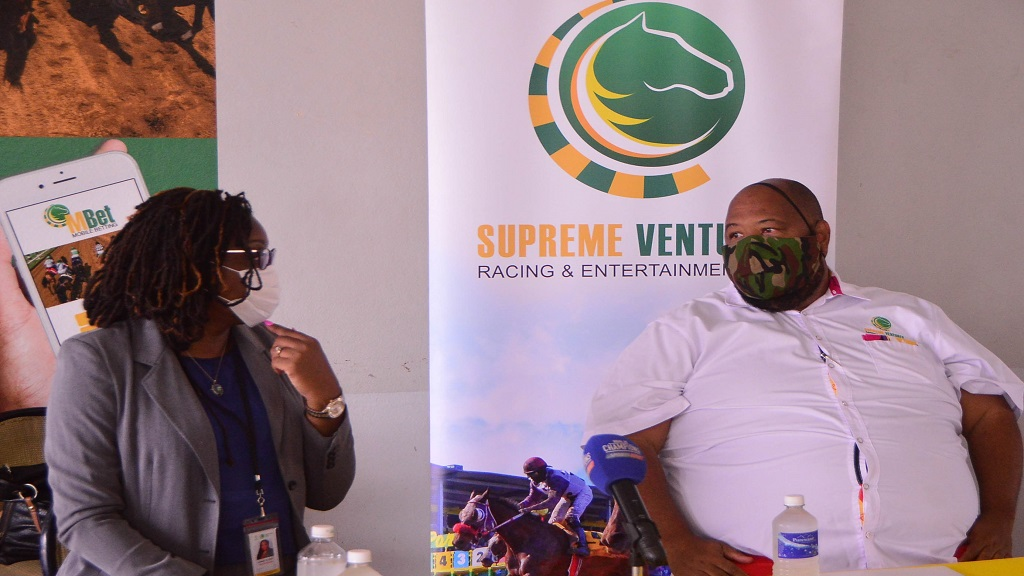 Lorna Gooden (left), general manager of Supreme Ventures Racing and Entertainment Limited (SVREL),  gets the attention of board's chairman Solomon Sharpe during a press conference at Caymanas Park on Monday, July 13, 2020.
