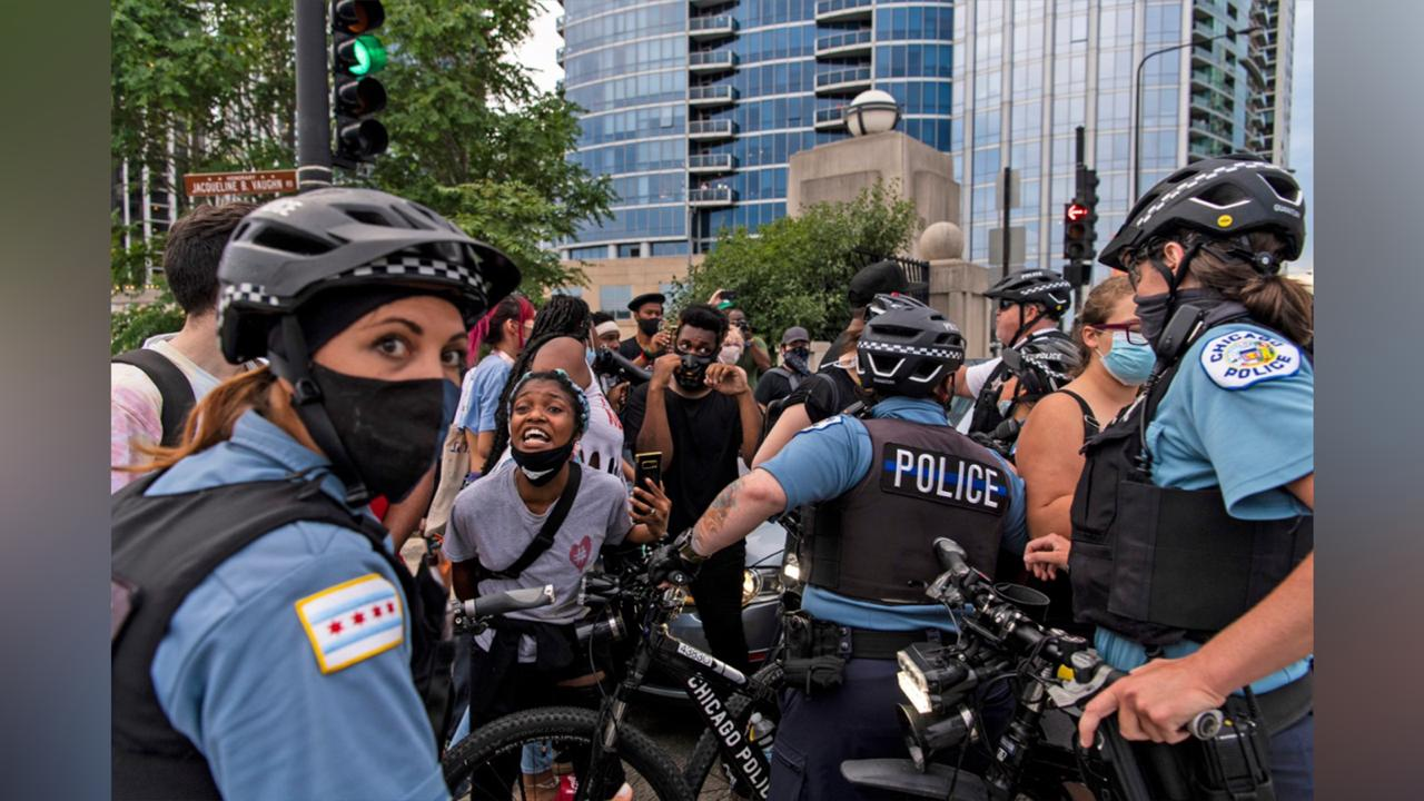 Chicago police and activists crowd around a vehicle that tried to drive through the protesters circle at the intersection of Roosevelt Rd. and Columbus Dr, Monday, July 20, 2020 in Chicago. (Tyler LaRiviere/Chicago Sun-Times via AP)
