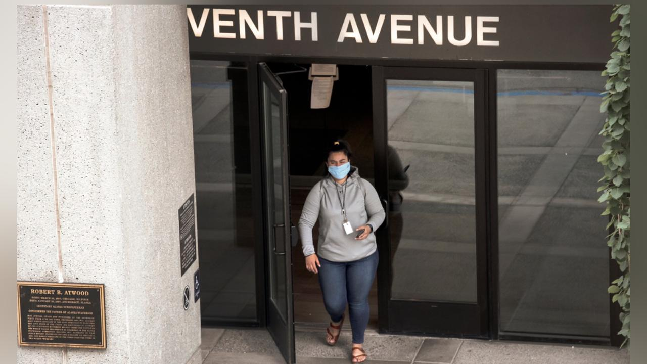 A woman wearing a face mask exits the Atwood Building, a downtown Anchorage, Alaska, building where many state offices are located on Monday, June 29, 2020. (AP Photo/Mark Thiessen)