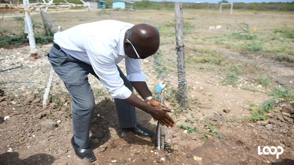 South East Clarendon MP, Pearnel Charles Jr samples the piped water.