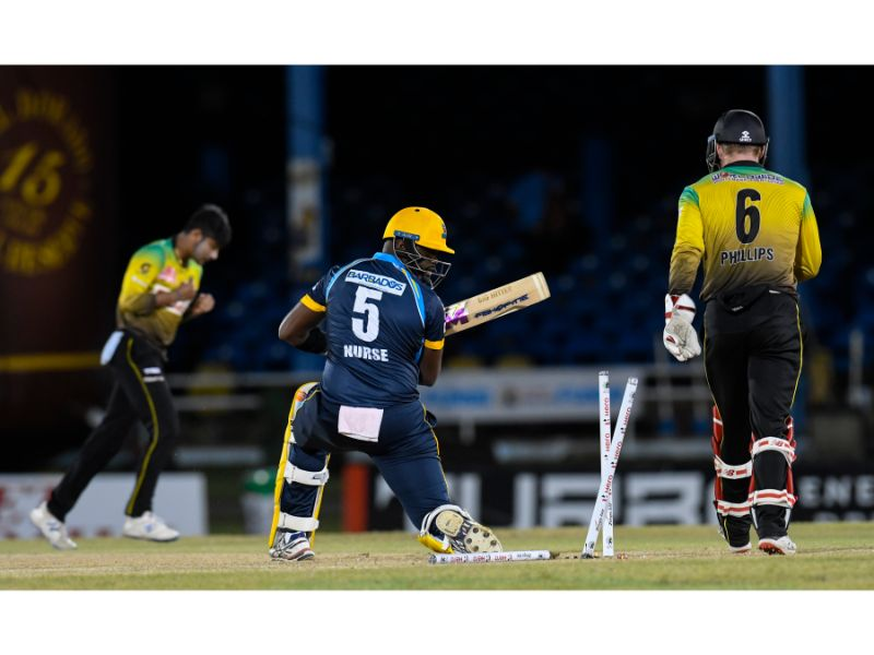Sandeep Lamichhane (left) of the Jamaica Tallawahs bowls Ashley Nurse, as Glenn Phillips (right) watches on during Match 14 of the Hero Caribbean Premier League match on 26th August 2020 at the Queen's Park Oval. (Photo by Randy Brooks - CPL T20/Getty Images)
