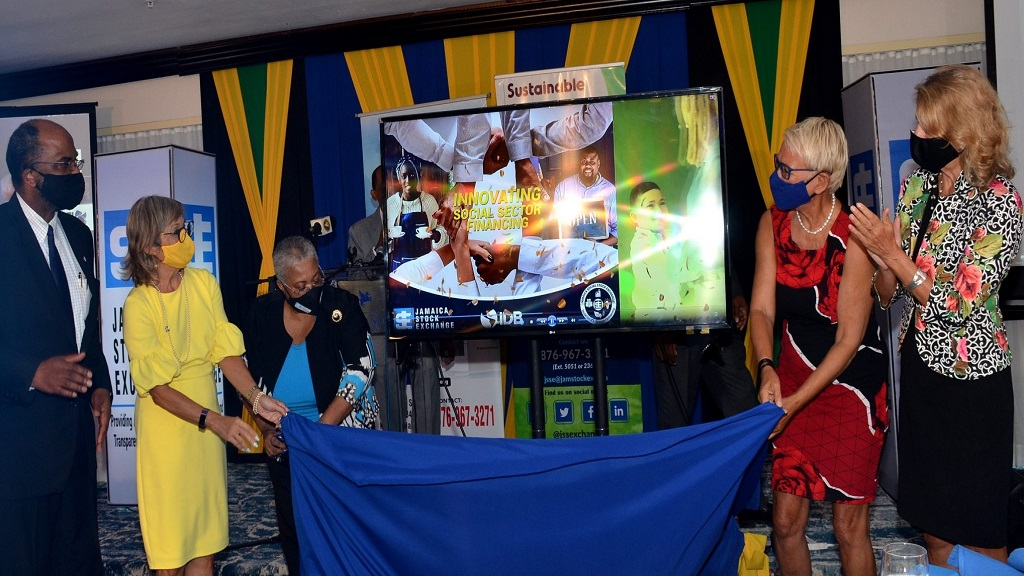 JSE Managing Director, Marlene Street Forest (centre), is assisted in unveiling the electronic banner for the 'Innovating Social Sector Financing' Project. Assisting her are JSSE Ambassador, Thalia Lyn (2nd left); and outgoing Head of Delegation of the European Union to Jamaica, Ambassador Malgorzata Wasilewska (2nd right). Observing (from left) are JN Group CEO, Earl Jarrett, who was the keynote speaker; and outgoing Canadian High Commissioner to Jamaica, Laurie Peters.