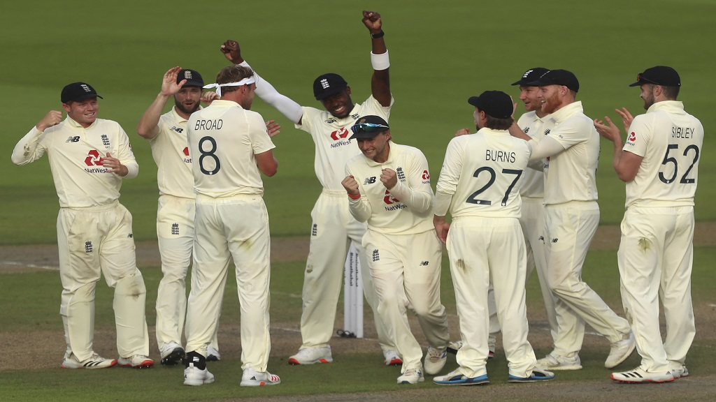 England's captain Joe Root, fifth right, and teammates celebrate the dismissal of Pakistan's Shadab Khan during the third day of the first cricket Test match at Old Trafford in Manchester, England, Friday, Aug. 7, 2020. (Lee Smith/Pool via AP).