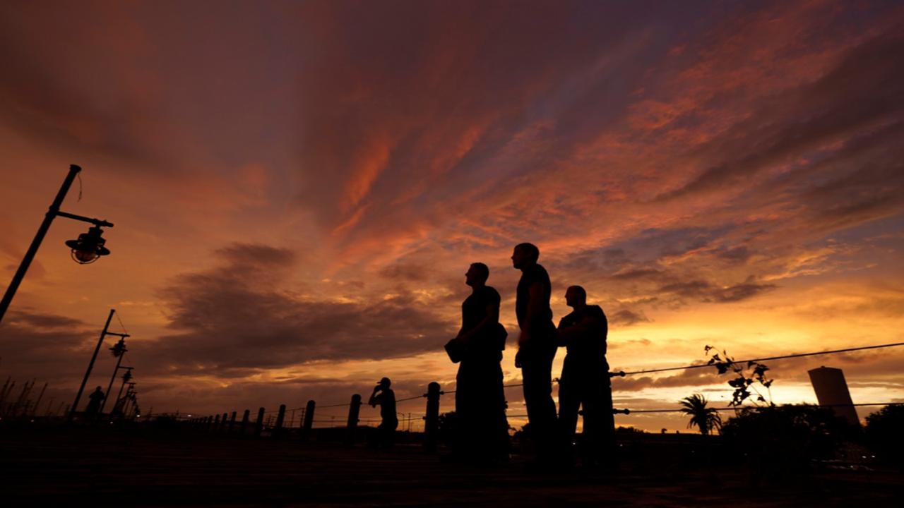 Port Arthur firefighters stare at a sea wall at sunset as they wait for Hurricane Laura to make landfall, Wednesday, Aug. 26, 2020, in Port Arthur, Texas. (AP Photo/Eric Gay)