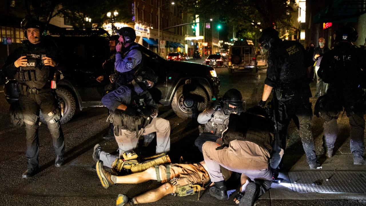 A man is treated after being shot Saturday, Aug. 29, 2020, in Portland, Ore. It wasn't clear if the fatal shooting late Saturday was linked to fights that broke out as a caravan of about 600 vehicles was confronted by counter demonstrators in the city's downtown. (AP Photo/Paula Bronstein)