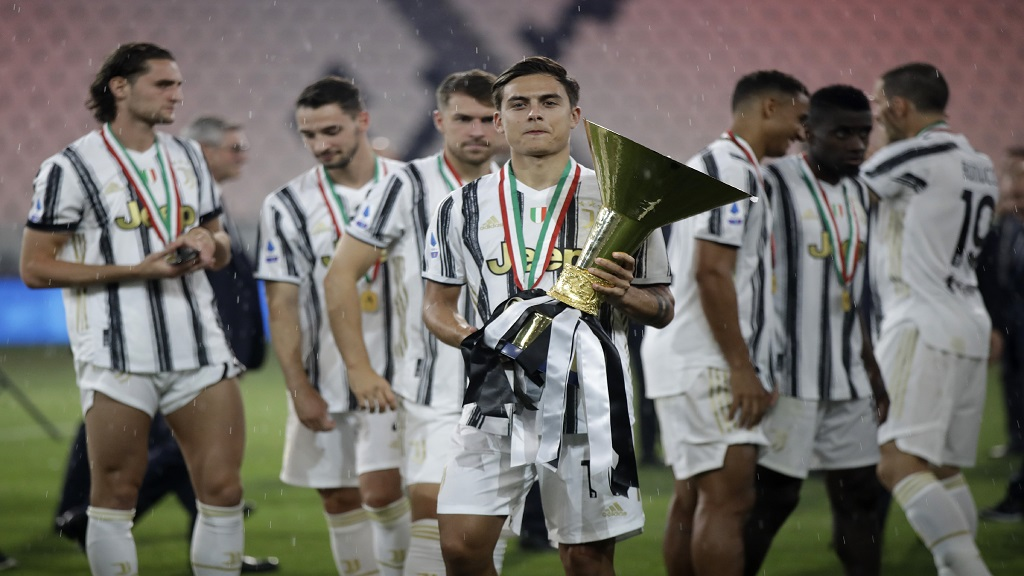 Paulo Dybala poses for photograph as he holds the trophy while his Juventus teammates celebrate winning an unprecedented ninth consecutive Italian Serie A football title, at the end of the a Serie A match against Roma, at the Allianz stadium in Turin, Italy, Saturday, Aug.1, 2020. (AP Photo/Luca Bruno).