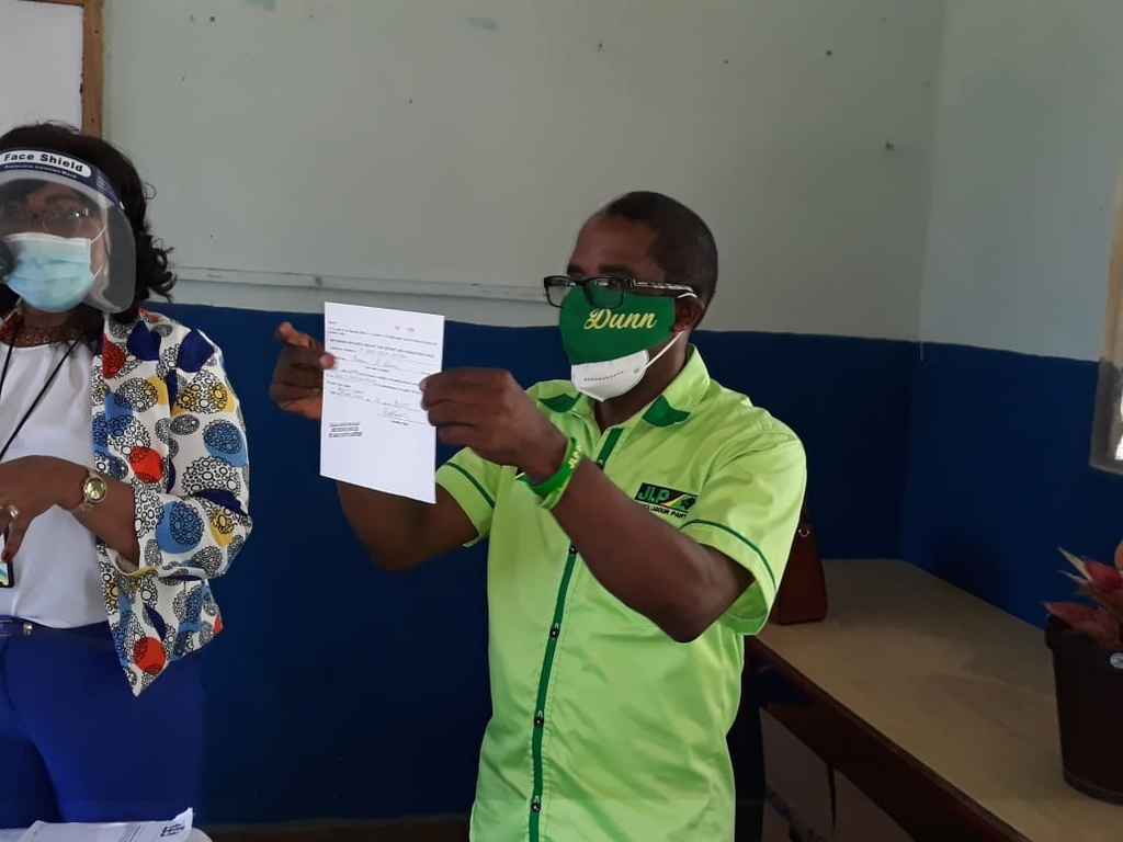 The JLP's candidate for South East St Mary, Dr Norman Dunn shows off his nomination papers.