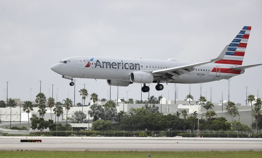 FILE - An American Airlines Boeing 737-823 lands at Miami International Airport, Monday, July 27, 2020, in Miami. American Airlines said Tuesday, August 25 that it will furlough or lay off 19,000 employees in October as it struggles with a sharp downturn in travel because of the pandemic. Flight attendants will bear the heaviest cuts, with 8,100 losing their jobs. (AP Photo/Wilfredo Lee, File)