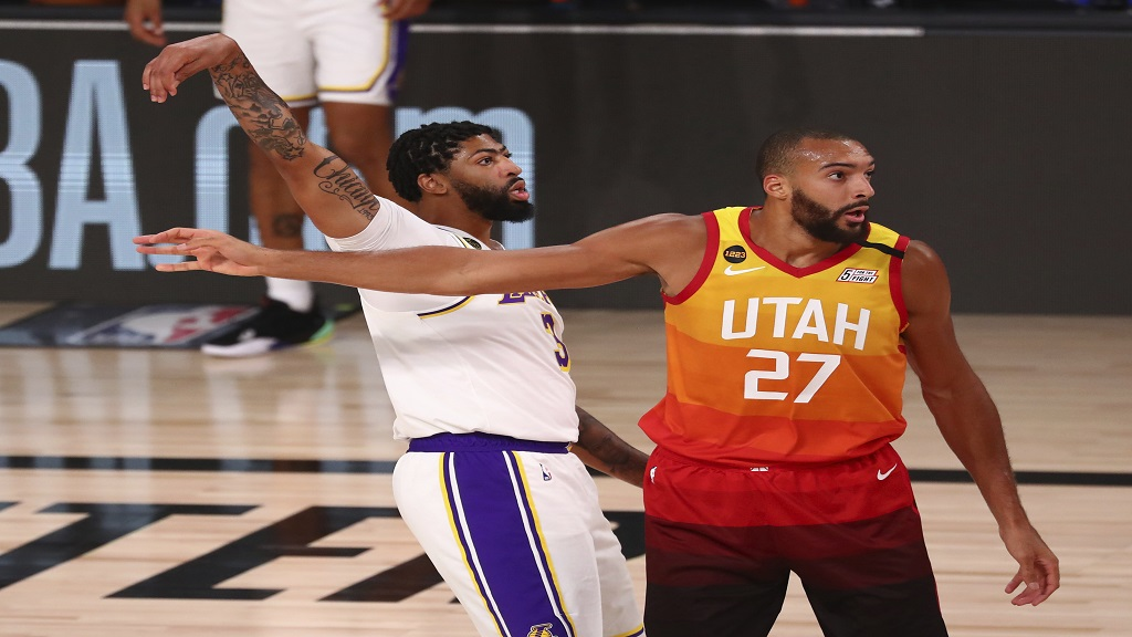 Los Angeles Lakers forward Anthony Davis (3) makes a three-point basket over Utah Jazz center Rudy Gobert (27) during the first half of an NBA basketball game Monday, Aug. 3, 2020, in Lake Buena Vista, Fla. (Kim Klement/Pool Photo via AP).