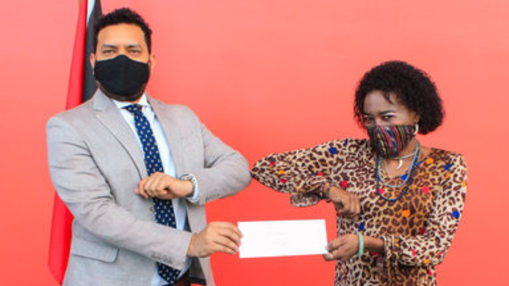 Pictured: Minister of Tourism, Culture and the Arts Randall Mitchell presents a cheque to Singing Sonia. Photo courtesy the Ministry of Tourism, Culture and the Arts.
