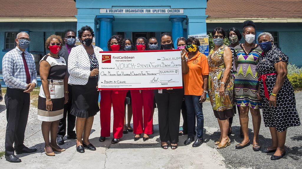 Alrea Washington Hoilett (2nd left), Chairman, Voluntary Organization for the Upliftment of Children (VOUCH) and Renee Whitehorne (8th left), Marketing Manager, CIBC FirstCaribbean International Bank, display the cheque for $1.4M donated by the bank through it Adopt-A-Cause programme for the upgrading of the Sylvia Foote Basic School at VOUCH.