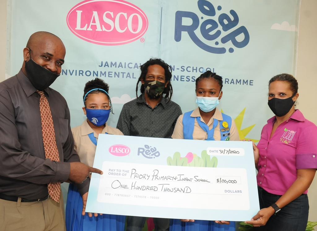 "Priory Primary and Infant School Principal Dwight Minto (left) accepts the champion's cheque for the ""Most Trees Planted"" valued at $100,000 from LASCO Distributors Limited Beverage Marketing Manager Danielle Cunningham (right). Sharing the moment are Priory Primary and Infant students Mikayla Minto (second left); Lillianna Jackson (second right) and Founder and Director of REAP, Stephen Newland."