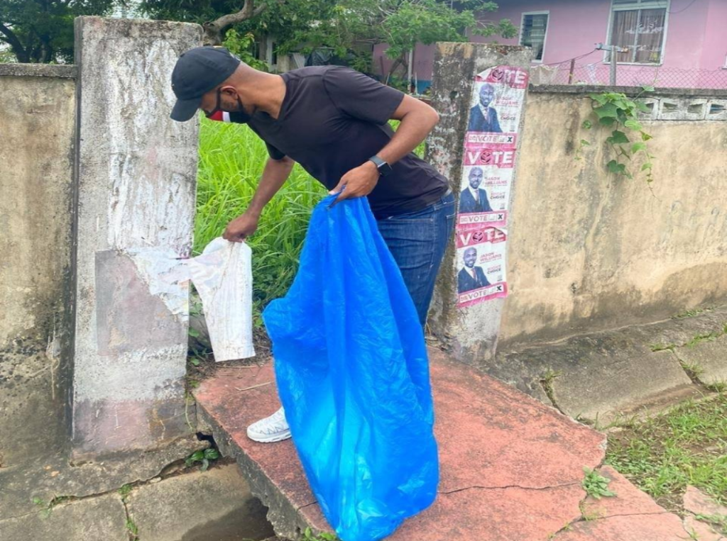 Pictured: Jason Williams removes election posters in Barataria. Photo via Facebook, Jason Williams - PNM Candidate 2020.