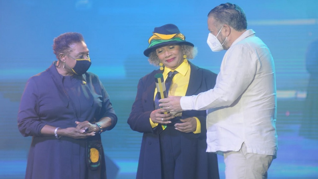 'Queen of Reggae' Marcia Griffiths (centre) being honoured for her contribution to Jamaican music at the Jamaica 58 Independence Spectacular on Thursday. Culture Minister Olivia Grange and Government Senator Tom Tavares Finson share in the occasion.