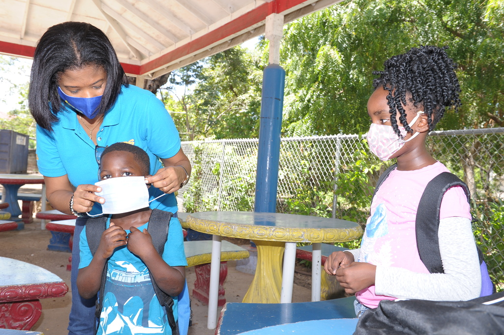 Marilyn McDonald, JPS' Community Renewal Manager helps a young boy put on his face mask Standpipe in St Andrew.