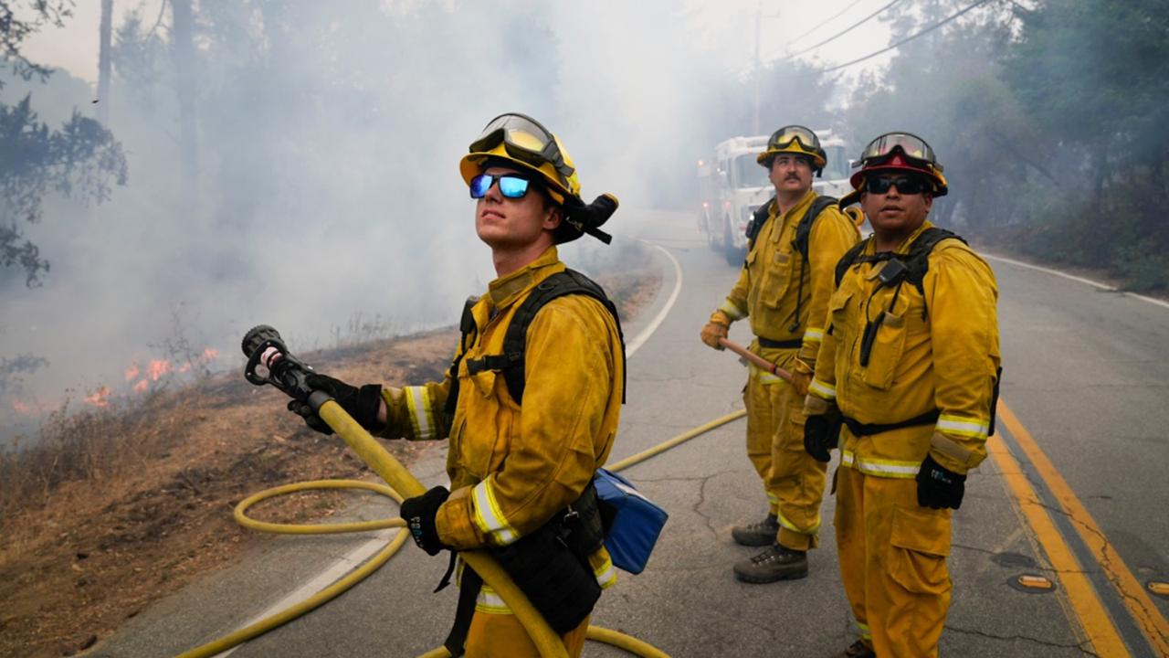 Firefighters Cody Nordstrom, Kyle Harp and Robert Gonzalez, from left, of the North Central Fire station out of Kerman, Calif., look up at a water-dropping helicopter while fighting the CZU Lightning Complex Fire on Sunday, Aug. 23, 2020, in Bonny Doon, Calif. (AP Photo/Marcio Jose Sanchez)