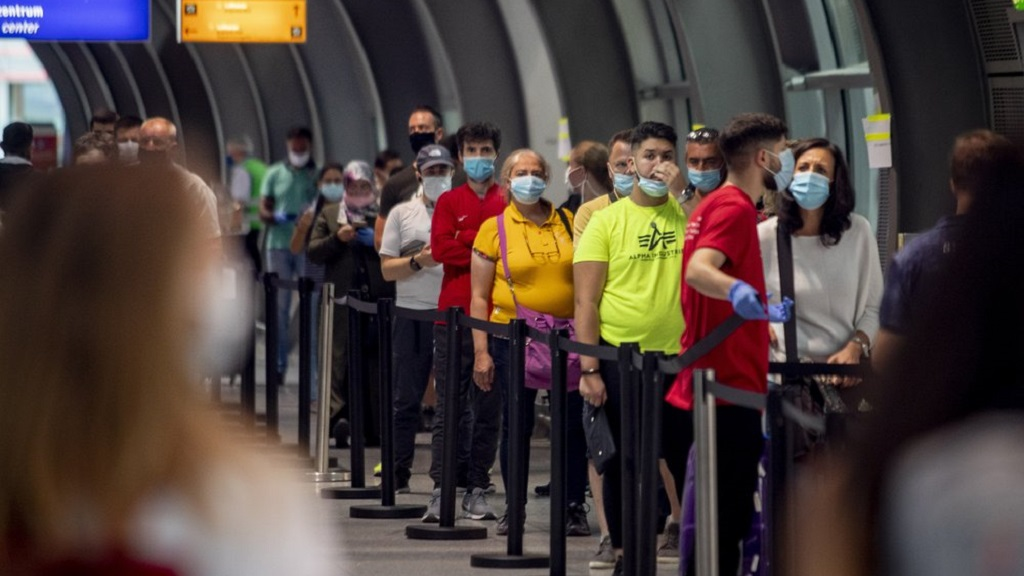 Passenger queue at the Covid-19 test station at the airport in Frankfurt, Germany, Monday, Aug. 3, 2020. (AP Photo/Michael Probst)