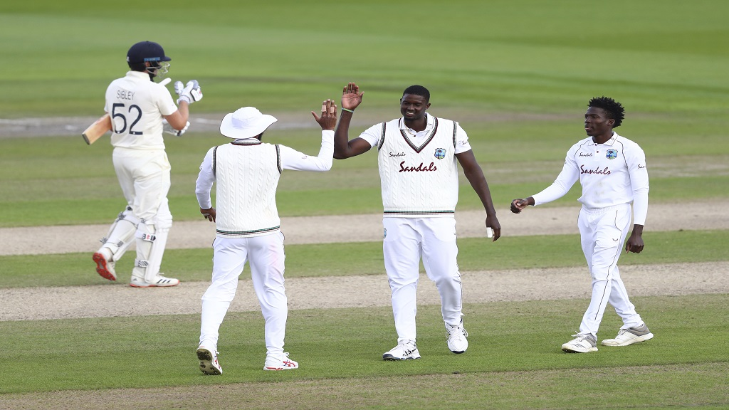 West Indies' captain Jason Holder, second right, celebrates with teammates the dismissal of England's Dom Sibley, left, during the third day of the deciding third cricket Test match at Old Trafford in Manchester, England, Sunday, July 26, 2020. (Michael Steele/Pool via AP).