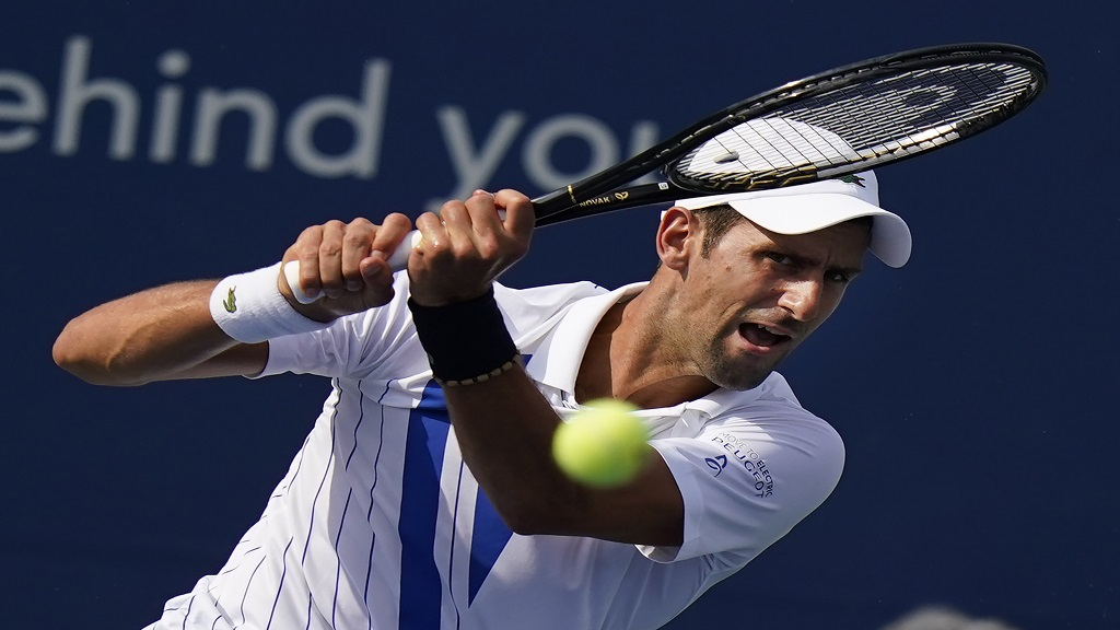 Novak Djokovic, of Serbia, returns a shot from Tennys Sandgren during the third round at the Western & Southern Open tennis tournament Tuesday, Aug. 25, 2020, in New York. (AP Photo/Frank Franklin II).