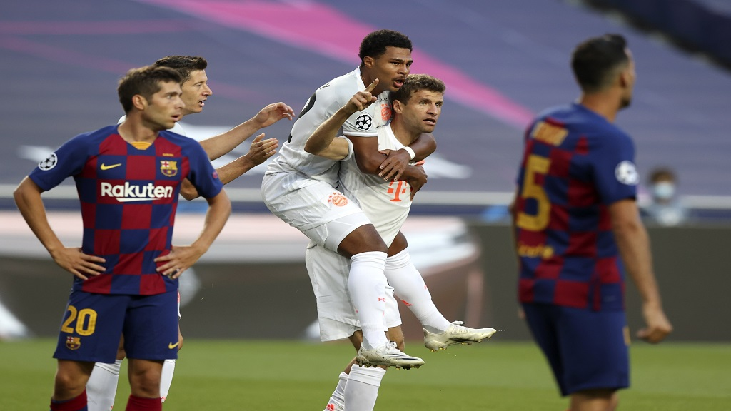 Bayern's Thomas Mueller, bottom centre, celebrates after scoring the opening goal during the Champions League quarterfinal football match against Barcelona  in Lisbon, Portugal, Friday, Aug. 14, 2020. (Rafael Marchante/Pool via AP).