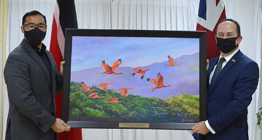 """Minister of National Security Stuart Young (left) presents UK High Commissioner Trinidad and Tobago Tim Stew (right) with a local painting entitled """"Ibises in Flight"""" by Artist Hayden Geeawan as a token of appreciation."""