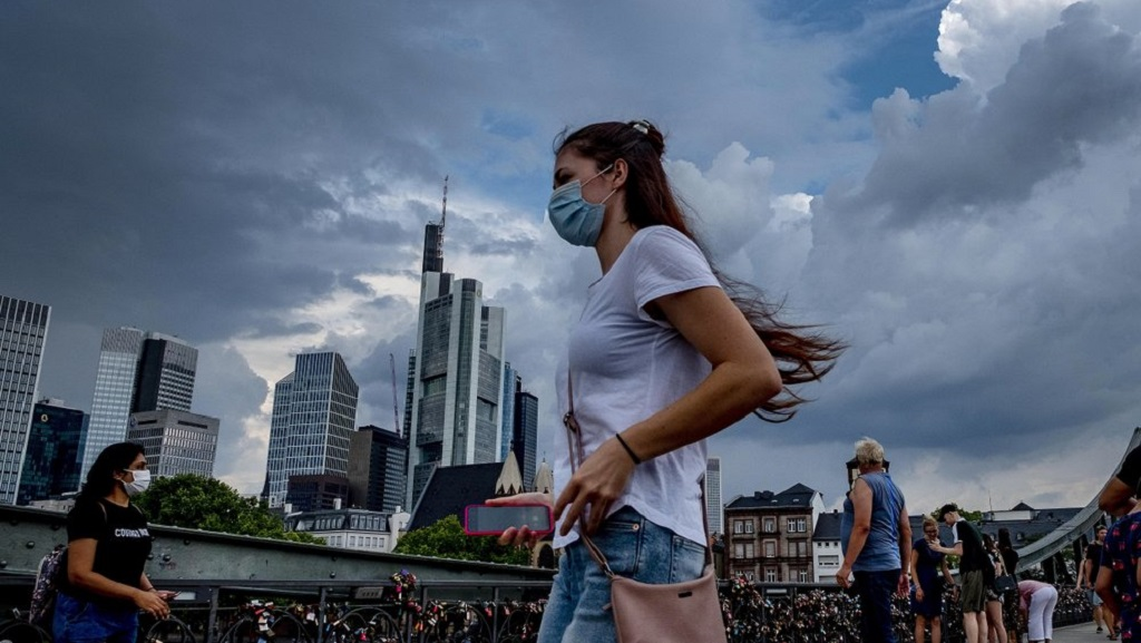 A young woman wears a face mask as she walks on a pedestrian bridge in Frankfurt, Germany, Saturday, Aug. 15, 2020. In background the buildings of the banking district. (AP Photo/Michael Probst)