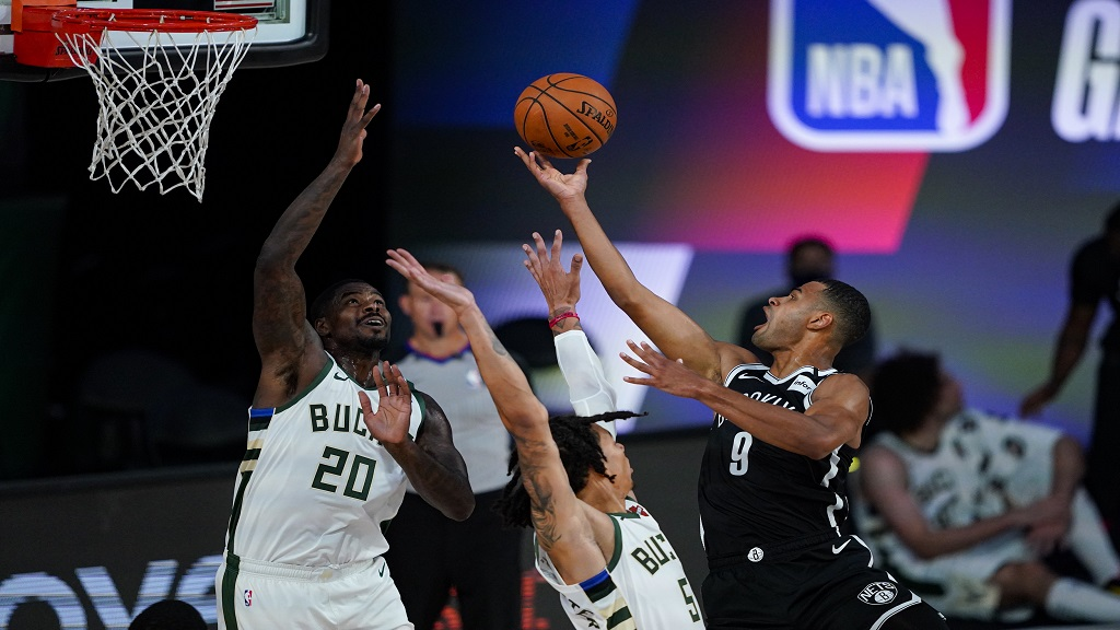 Brooklyn Nets guard Timothe Luwawu-Cabarrot (9) shoots over Milwaukee Bucks forward Marvin Williams (20) and forward D.J. Wilson (5) during the second half of an NBA basketball game Tuesday, Aug. 4, 2020 in Lake Buena Vista, Fla. (AP Photo/Ashley Landis).