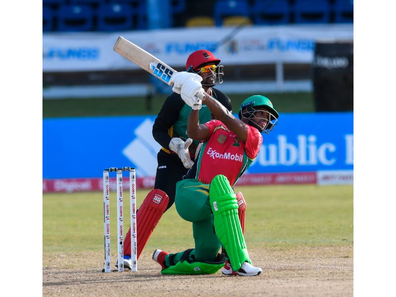 Guyana Amazon Warriors batsman NIcholas Pooran hits another six, as St Kitts and Patriots keeper Denesh Ramdin looks on, during his innings of 100* not out at the Queen's Park Oval on Sunday in the Hero Caribbean Premier League. (Photo by Randy Brooks - CPL T20/Getty Images)