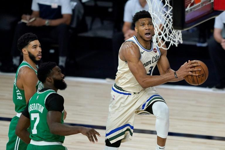 Milwaukee Bucks star Giannis Antetokounmpo, right, drives past Boston's Jaylen Brown, 7, to the basket during the first half of an NBA game Friday in Orlando, Florida
