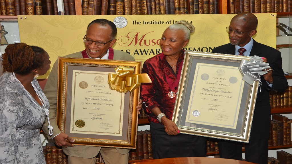 In this January 2016 JIS photo, Executive Director of the Institute of Jamaica (IOJ), Anne-Marie Bonner (left), congratulates recipient of the 2015 Musgrave Gold Medal Award, Professor Orlando Patterson (2nd left), and Silver Medal awardee, Dr. Myrna Hague-Bradshaw, at the presentation ceremony held on Monday (January 4), at the Institute's downtown Kingston headquarters. Looking at right is Chairman of the IOJ's Council, Ambassador Burchell Whiteman.
