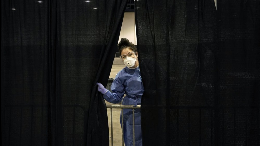 Diana Vega, a registered respiratory therapist, peeks through a curtain during setup at a temporary coronavirus testing site Monday, Aug. 3, 2020, in Las Vegas. (AP Photo/John Locher)