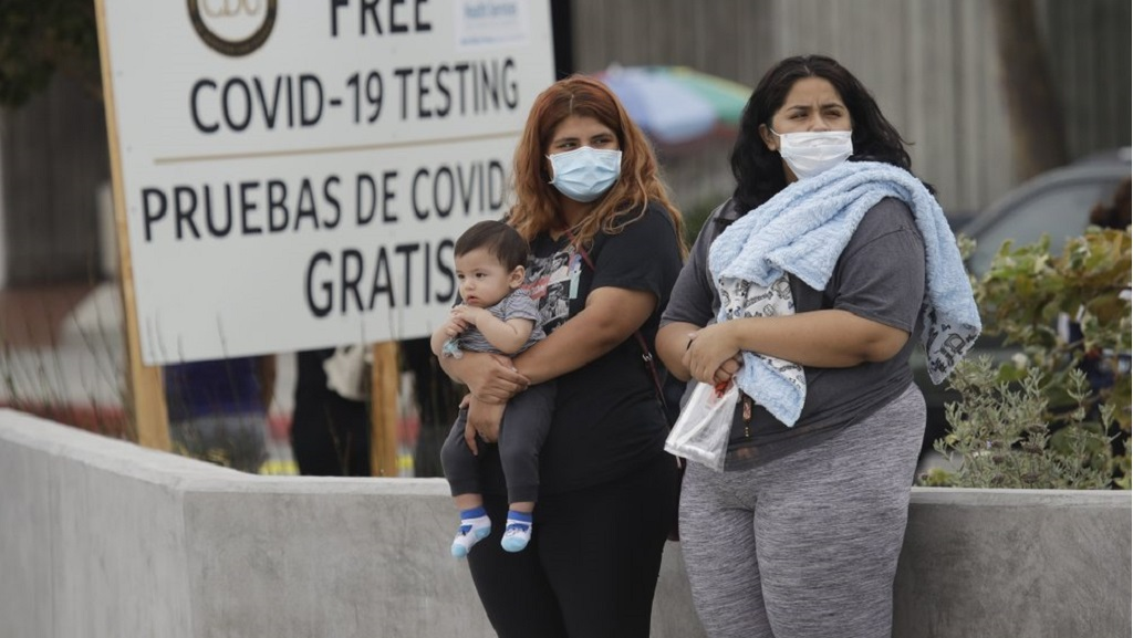 Two women and a child wait to take a Coronavirus test at a mobile testing site at the Charles Drew University of Medicine and Science Wednesday, July 22, 2020, in Los Angeles. California's confirmed coronavirus cases have topped 409,000, surpassing New York for most in the nation. (AP Photo/Marcio Jose Sanchez)