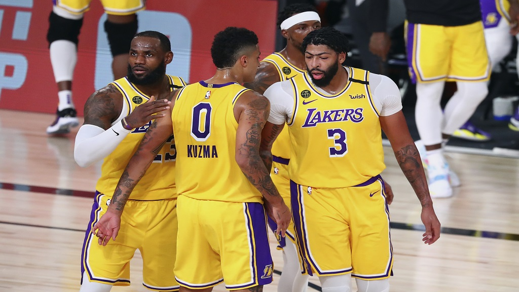 Los Angeles Lakers forward LeBron James (23), forward Kyle Kuzma (0), guard Kentavious Caldwell-Pope, second from right, and forward Anthony Davis (3) huddle during the first half against the Portland Trail Blazers during Game 2 of an NBA basketball first-round playoff series, Thursday, Aug. 20, 2020, in Lake Buena Vista, Fla. (Kim Klement/Pool Photo via AP).