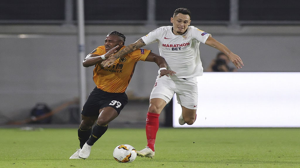 Wolverhampton Wanderers' Adama Traore, left, challenges for the ball with Sevilla's Lucas Ocampos during the Europa League quarterfinal football match at the MSV Arena in Duisburg, Germany, Tuesday, Aug. 11, 2020. (Friedemann Vogel, Pool Photo via AP).