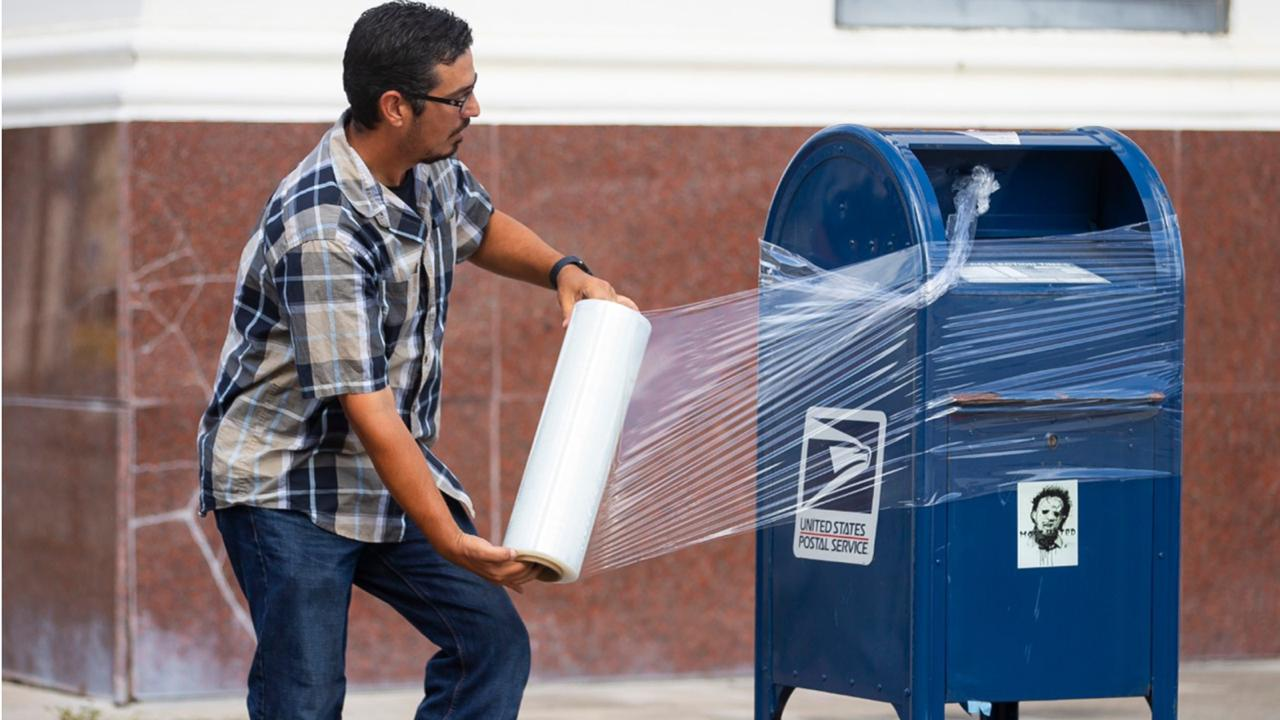 A United State Postal Service Employee covers a mailbox with plastic wrap after removing the last mail from it as the island prepares for possible impact from Hurricane Laura, Tuesday, Aug. 25, 2020, in Galveston. The plastic wrap signals that the final mail has been cleared from the box and prevents people from placing more mail inside in case of flooding. (Mark Mulligan/Houston Chronicle via AP)