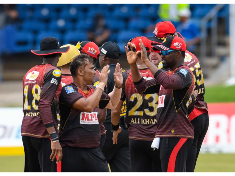TKR's Pravin Tambe (left front) celebrates his first CPL wicket with Darren Bravo (right front).