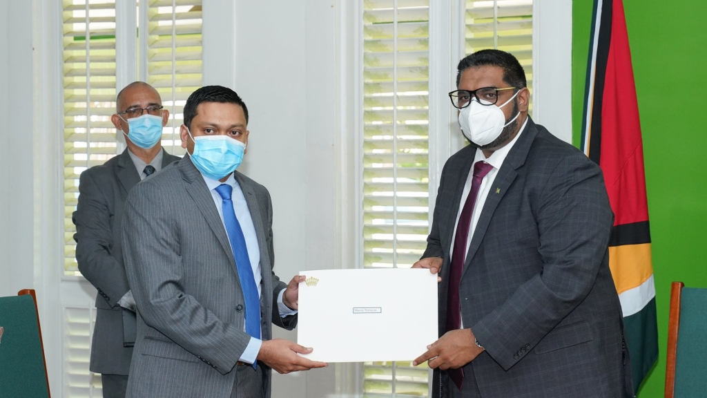 President Dr Mohamed Irfaan Ali presents the Instrument of Appointment to Manoj Narayan at State House. Photo: Office of the President