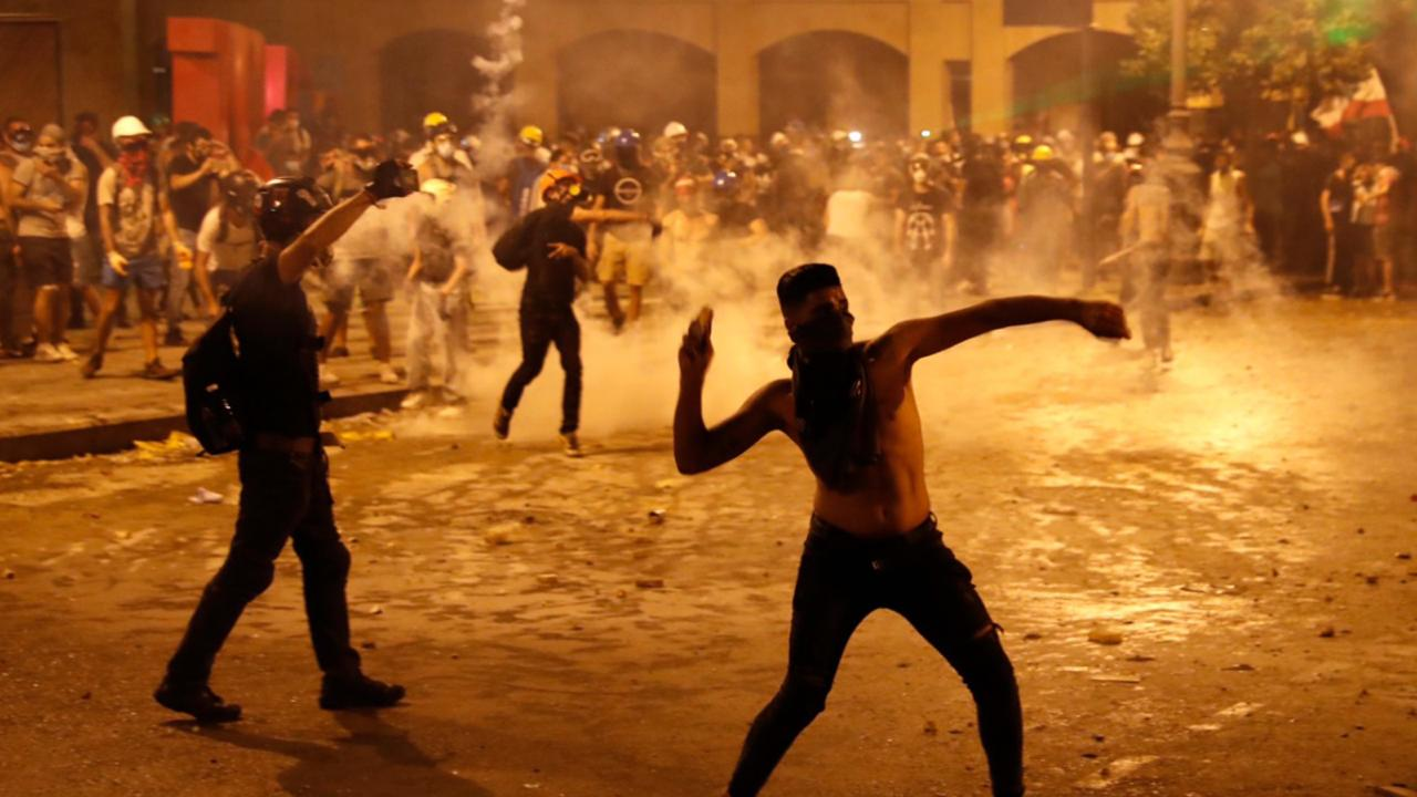 A protester throw stones against the Lebanese riot police, during anti-government protest following Tuesday's massive explosion which devastated Beirut, Lebanon, Sunday, Aug. 9. 2020. (AP Photo/Hussein Malla)