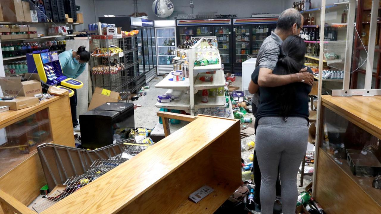 Yogi Dalal hugs his daughter Jigisha as his other daughter Kajal, left, bows her head at the family food and liquor store Monday, Aug. 10, 2020, after the family business was vandalized in Chicago. Chicago's police commissioner says more than 100 people were arrested following a night of looting and unrest that left several officers injured and caused damage in the city's upscale Magnificent Mile shopping district and other parts of the city. (AP Photo/Charles Rex Arbogast)