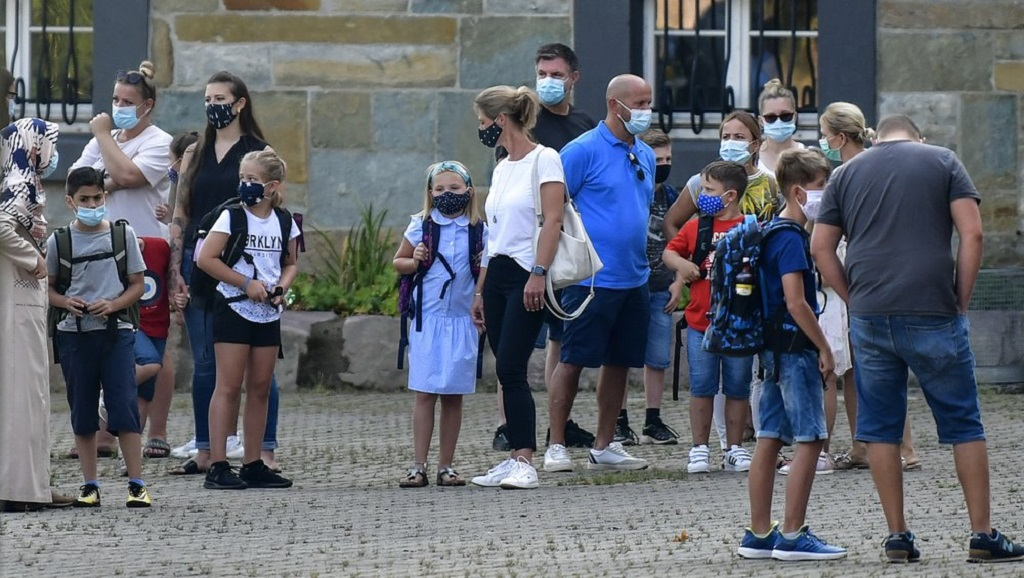 FILE - In this Wednesday, Aug. 12, 2020 file photo, parents wait with their children for the start of their first day of school in Gelsenkirchen, Germany. (AP Photo/Martin Meissner, File)