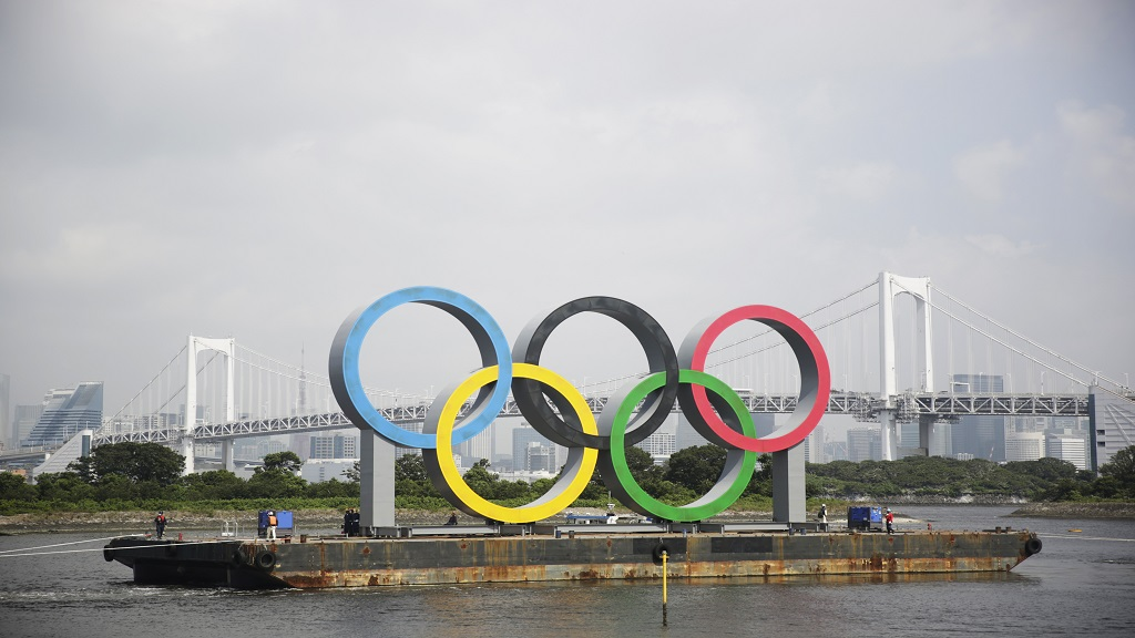 "A symbol installed for the Olympic and Paralympic Games Tokyo 2020 on a barge is moved away from its usual spot by tugboats off the Odaiba Marine Park in Tokyo Thursday, Aug. 6, 2020. The five Olympic rings floating on a barge in Tokyo Bay were removed for what is being called ""maintenance,"" and officials says they will return to greet next year's Games.  (AP Photo/Hiro Komae)."