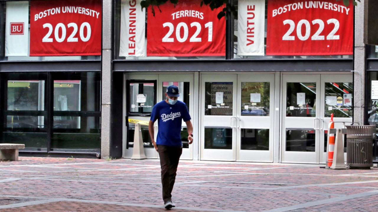In this July 23, 2020, file photo, Weston Koenn, a graduate student from Los Angeles, leaves the Boston University student union building as he walks through the student-less campus in Boston. As more universities keep classes online this fall, it's leading to conflict between students who say they deserve tuition discounts and college leaders who insist remote learning is worth the full cost. (AP Photo/Charles Krupa, File)