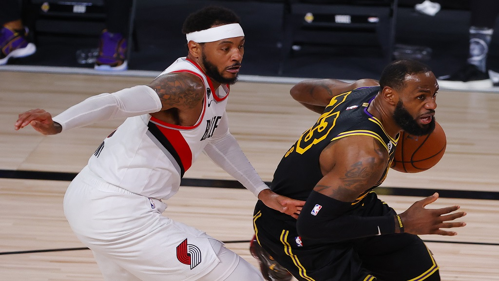 Los Angeles Lakers' LeBron James, right, drives against Portland Trail Blazers' Carmelo Anthony, left, during the second quarter of Game 4 of an NBA basketball first-round playoff series, Monday, Aug. 24, 2020, in Lake Buena Vista, Fla. (Kevin C. Cox/Pool Photo via AP).