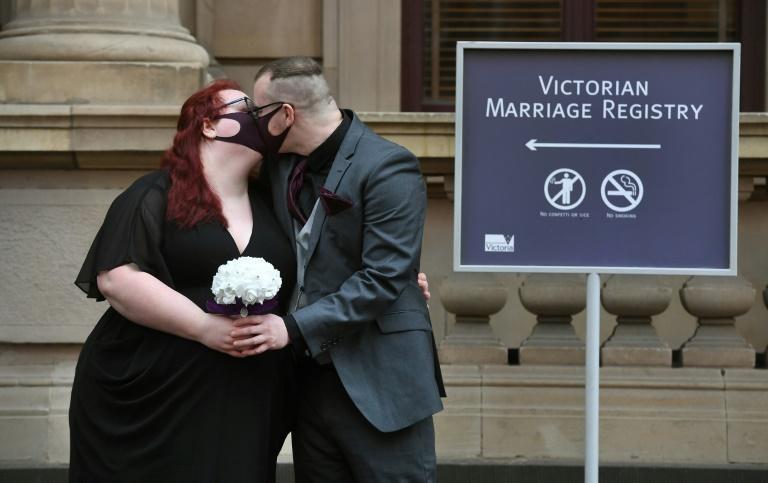 Un jeune couple s'embrasse après avoir célébré son mariage à Melbourne William WEST AFP
